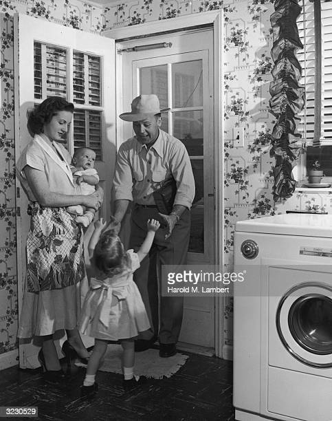 A man stands by a doorway holding his hands out to greet his daughter as his wife holds their baby A washing machine stands beside the door The man...