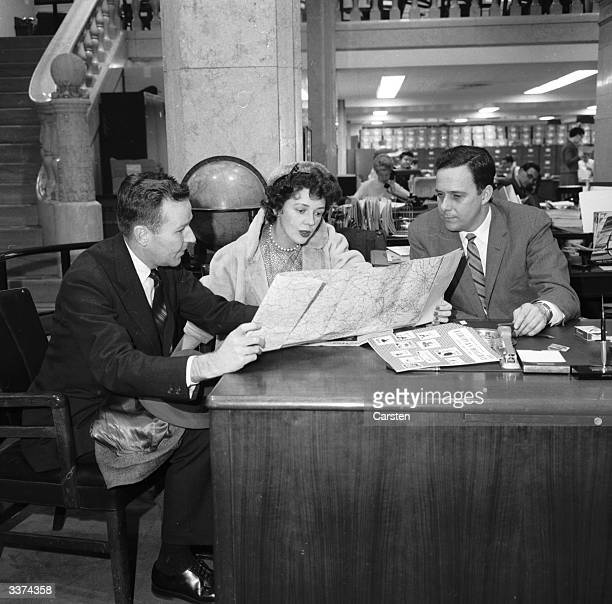 A manager at the American Express headquarters on Broadway New York advising a couple as they plan a trip around the world
