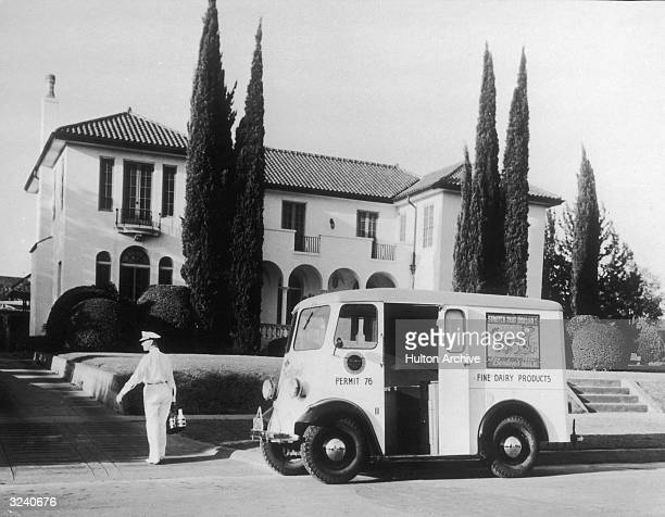 A milk man walks from his truck to a house carrying several bottles of milk Los Angeles California