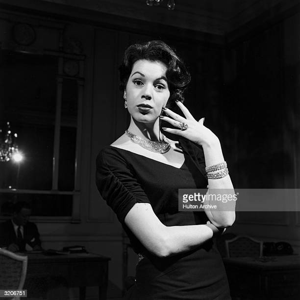 A model poses indoors in diamond jewelry including drop earrings a necklace a ring and bracelets from jeweler Harry Winston