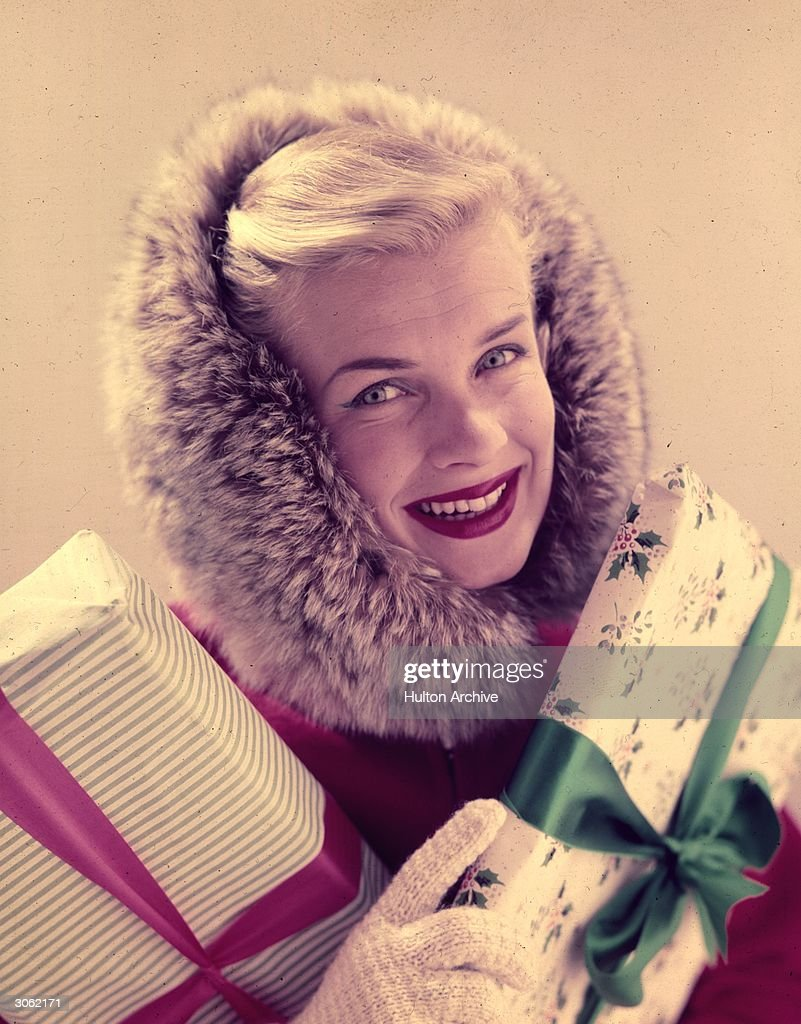 A model wearing a coat with a fur lined hood and carrying christmas presents.