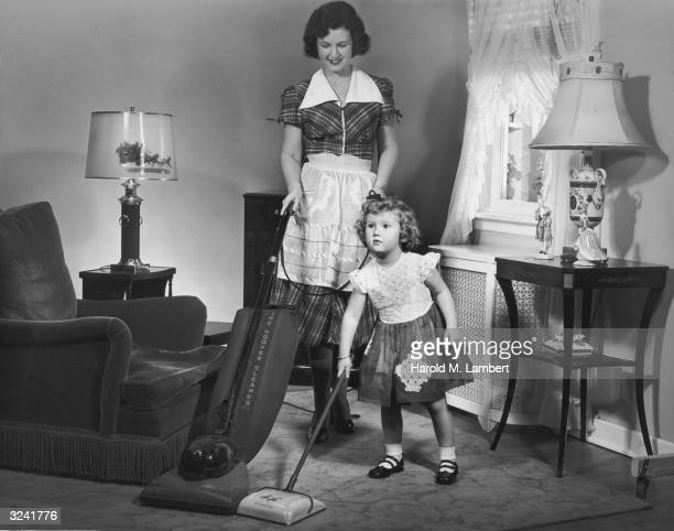 A mother and daughter vacuuming side by side in a living room 1950s The little girl is cleaning with a toy vacuum