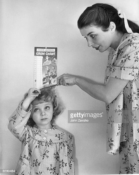 A mother smiles as she measures her daughter's height with a Grow Chart on the wall The girl holds a ruler above her head The mother and daughter are...