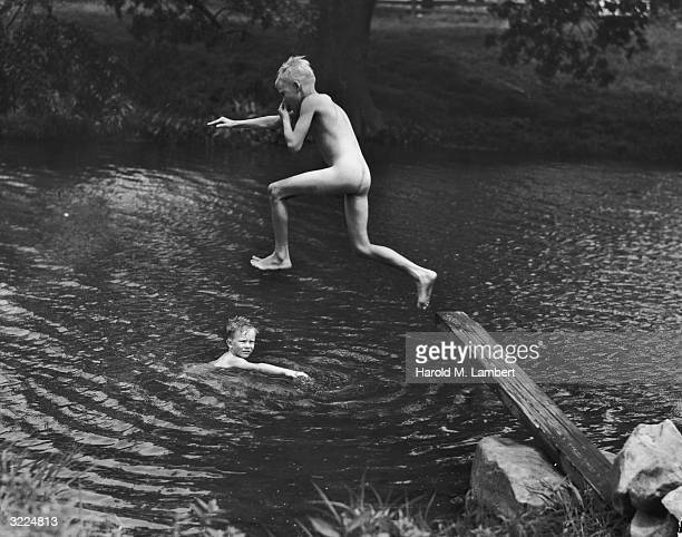A naked boy holds his nose as he takes a jump off a wooden plank into a river Another boy swims in the water