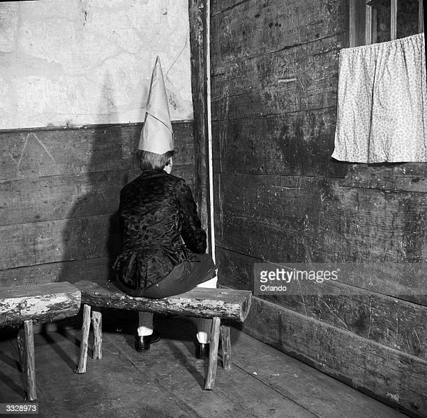 Naughty child sits in the corner and wears the dunce's cap, in a reconstruction of the old teaching methods and conditions at a one-room school in...