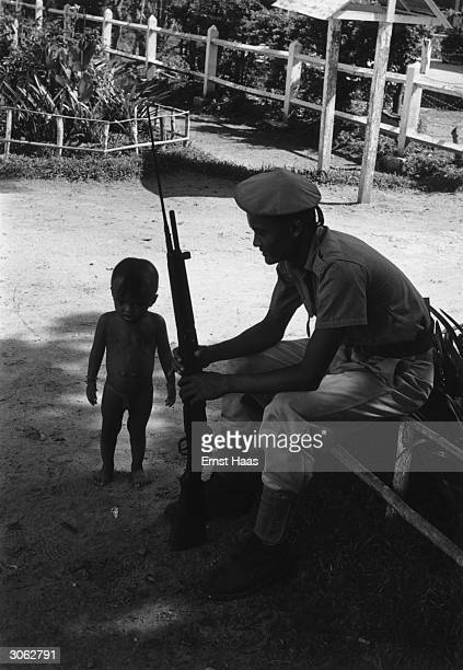 A nude little boy toddles past an armed soldier who is on duty in Angkor Wat near the temple of the Hindu god Vishnu
