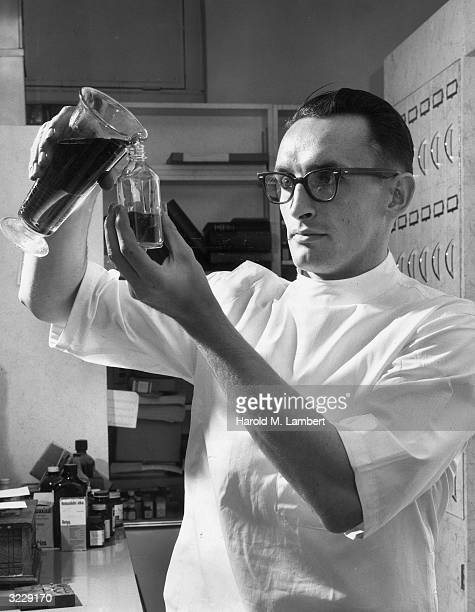 A pharmacist pours a solution from a beaker into a bottle He wears a white smock and dark hornrimmed eyeglasses