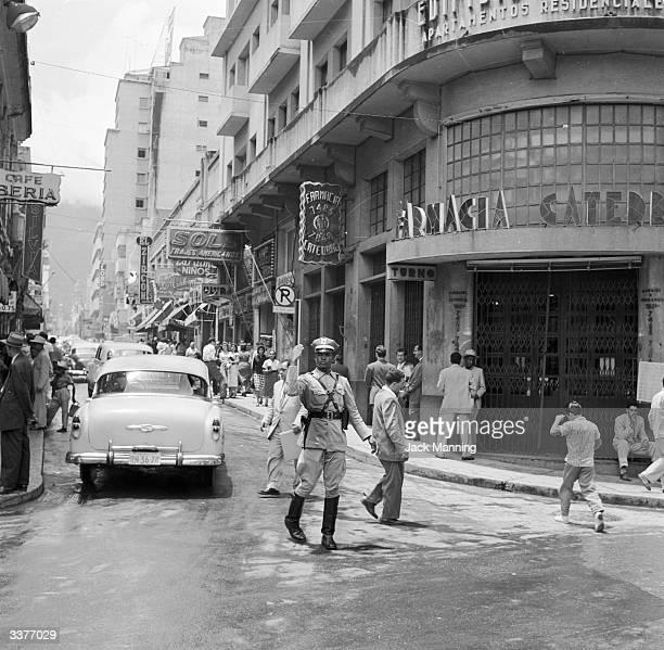 A policeman directing traffic around a busy corner of central Caracas Venezuela