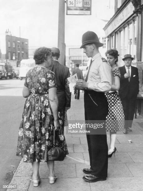 A policeman shows a woman in a Kennington bus queue an Identikit portrait of a murder suspect