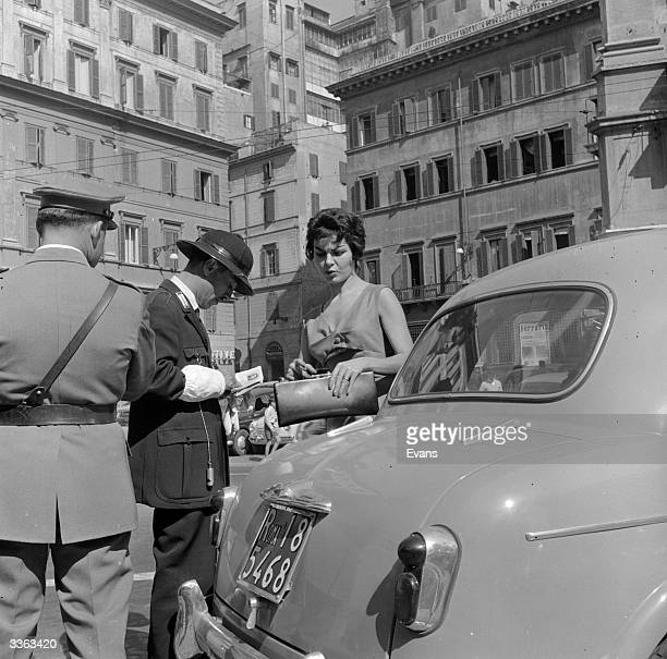 A policeman writes out a parking ticket as the driver looks on in the Piazza di Spagna Rome