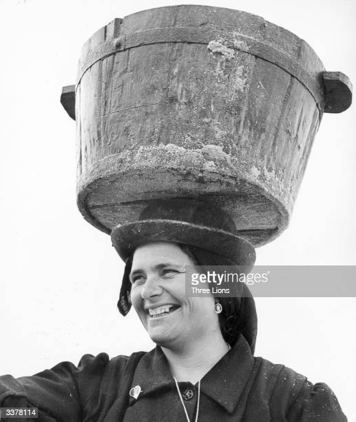 A Portuguese woman carries a tub laden with salt on her head from the nearby salt fields of Setubal near Lisbon