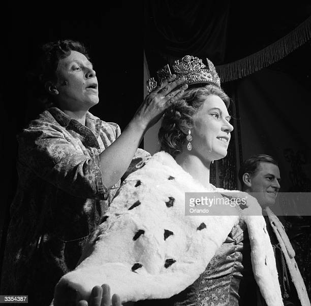 A replica of Queen Elizabeth II's crown being fitted to her waxwork effigy at Madame Tussaud's waxworks museum London