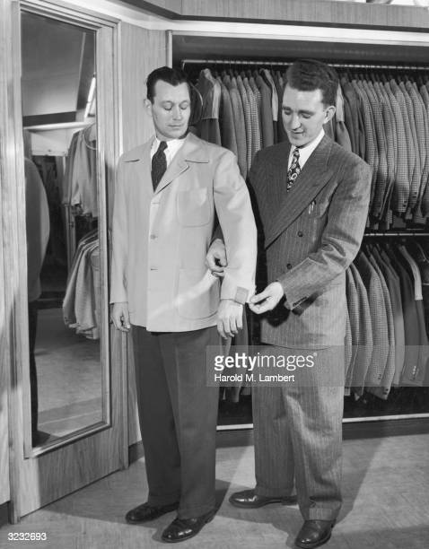 A salesman adjusts the sleeve of a jacket for a man in front of a mirror in a men's garment shop