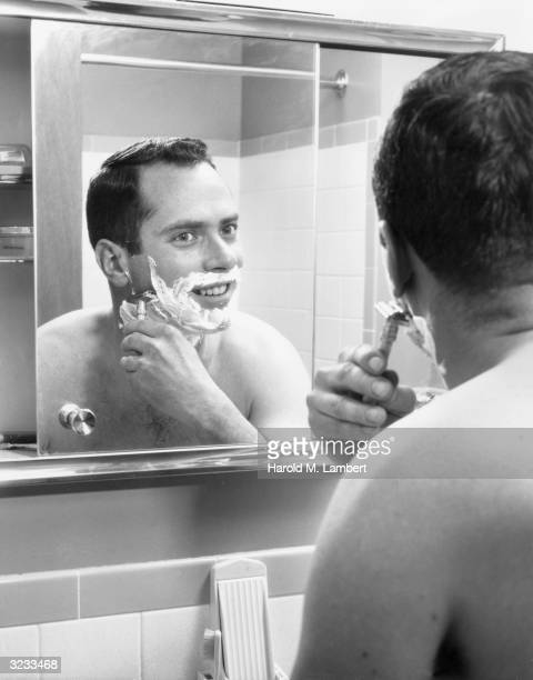 A shirtless man with shaving cream on his face looks into a bathroom mirror as he shaves with a safety razor