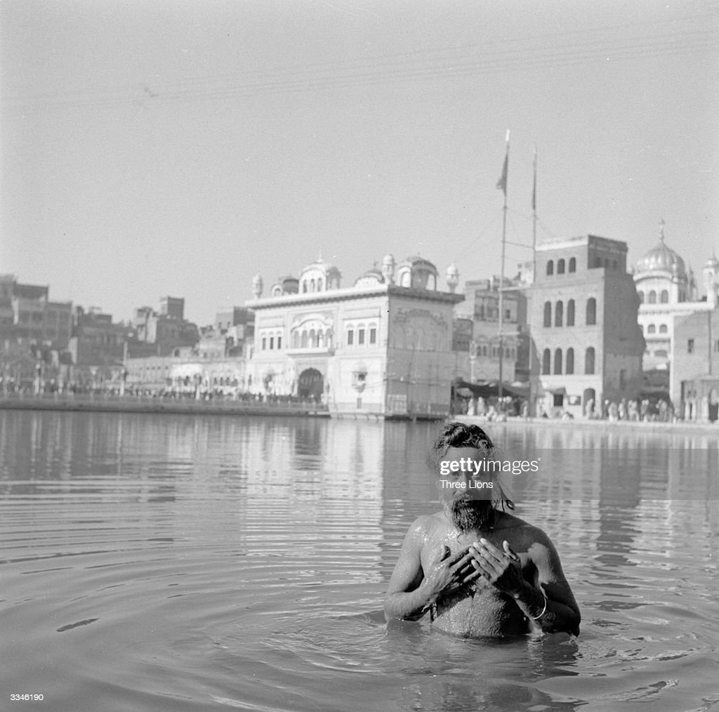 A Sikh man bathing in the waters at Harmandir Sahib or The Golden Temple Amritsar