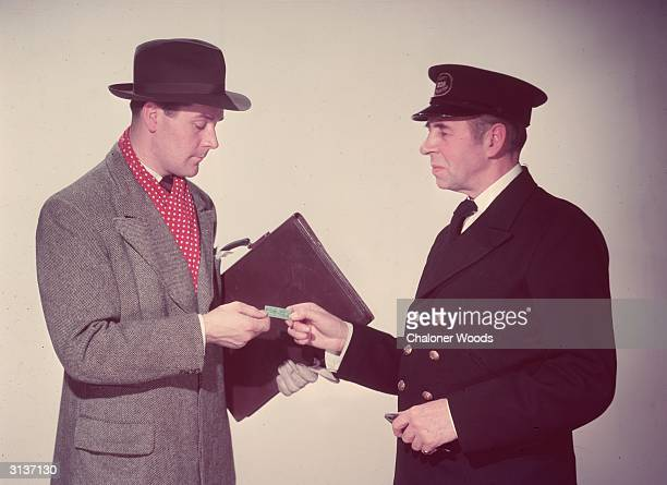 A smartly dressed traveller hands over his ticket to the railway inspector