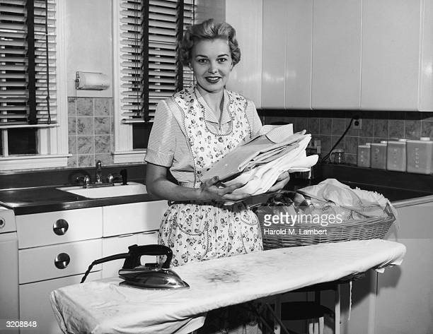 A smiling woman holding folded laundry standing next to an ironing board in a kitchen