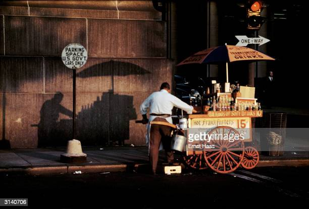 A street vendor pushes his hot dog stand through Greenwich Village in New York City Colour Photography book