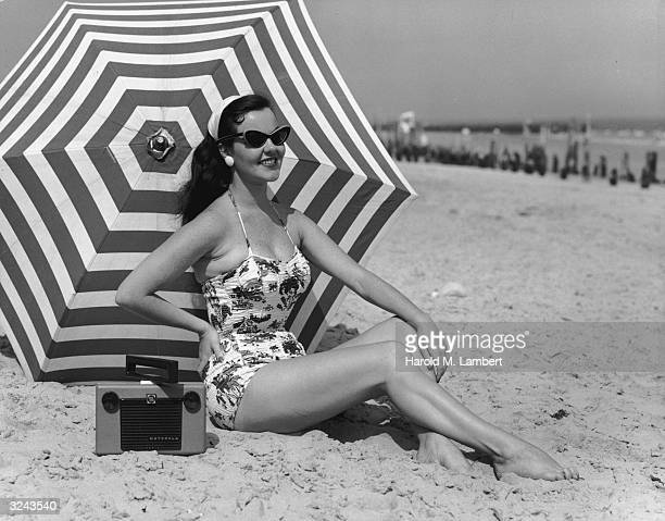 A swimsuitclad woman wearing cateye sunglasses poses on a beach with a radio and a striped beach umbrella