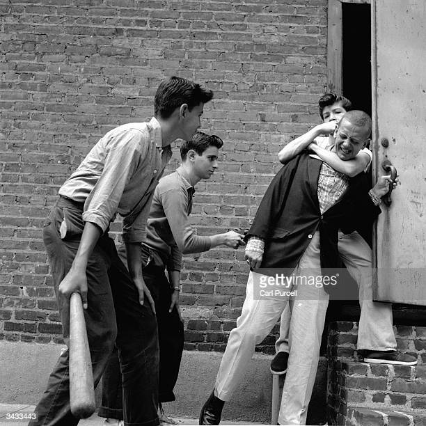 A teenage street gang carry out a mugging in a deserted alley in New York City
