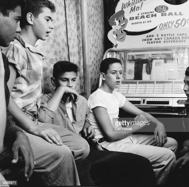 A teenage street gang hanging out in their local candy store in New York City