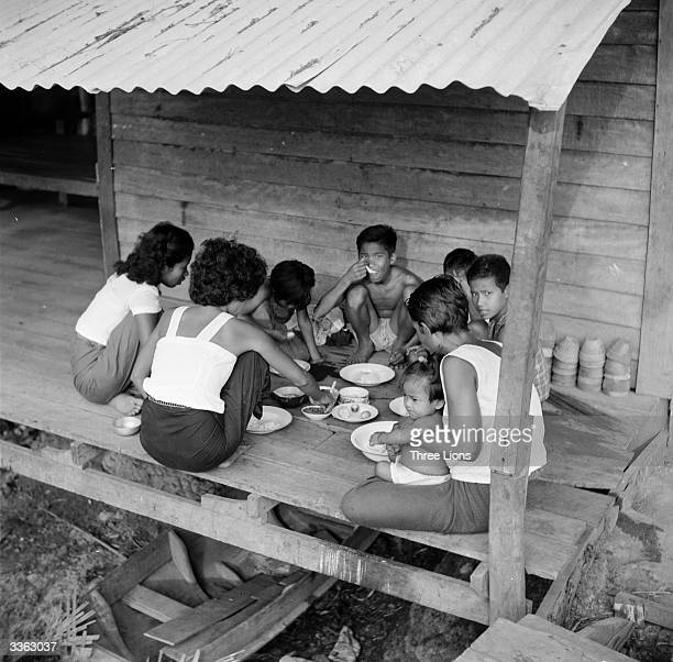 A Thai family eating in one of the many houses built on stilts on the banks of the Menam Chao Phya River in Bangkok