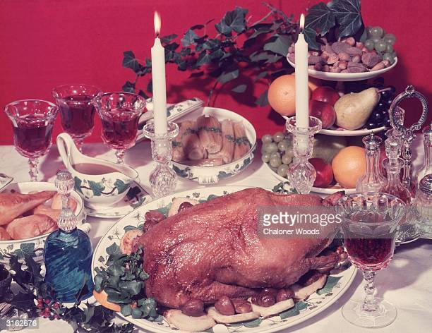 A traditional festive dinner table decorated with sprigs of berried holly