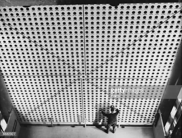 A wall of holes spaced eight inches apart where pure uranium is inserted into the atomic reactor at Brookhaven National Laboratories The platform...