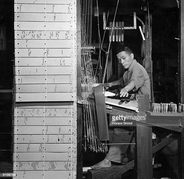A weaver at work on one of the Jacquard hand looms at a Nishijin plant in Kyoto Perforated patterned cards determine the woven design Rows of bobbins...