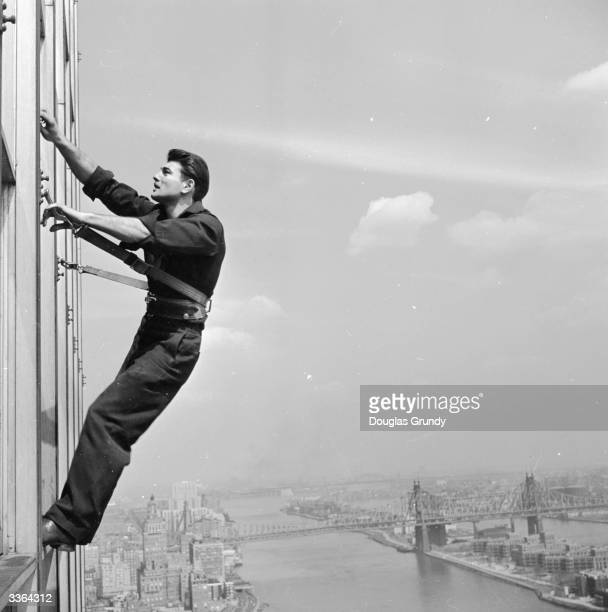 Window cleaner at work at the United Nations Secretariat building in mid-town Manhattan, overlooking the East River, New York. The building has 6,000...
