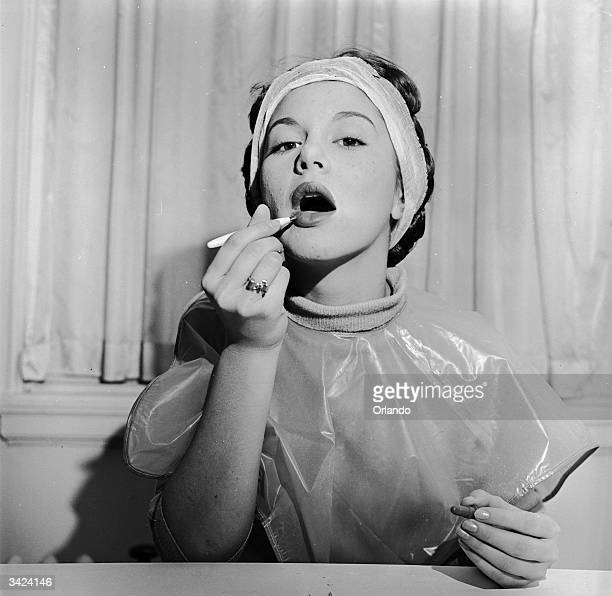 A woman applying her lipstick with a brush to ensure a good line