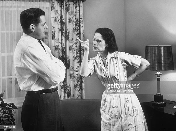 A woman gestures with her index finger as she scolds her husband who stands with his arms folded in front of a window with drapes She holds one hand...