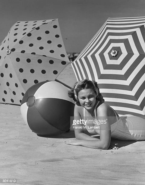 A woman in a one piece swimsuit smiles as she lays on her stomach beside a beach ball and two beach umbrellas