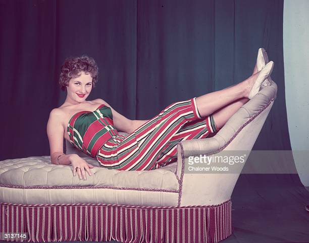 A woman lounging around in a red and green striped suit comprising a strapless top and pedal pushers