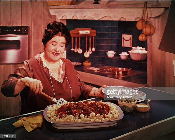 A woman prepares to serve pasta shells with tomato sauce from a large casserole dish while standing behind a counter in a kitchen