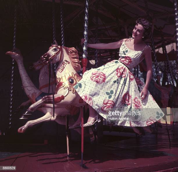 A woman riding the merrygoround at Battersea funfair wearing a floral print sun dress