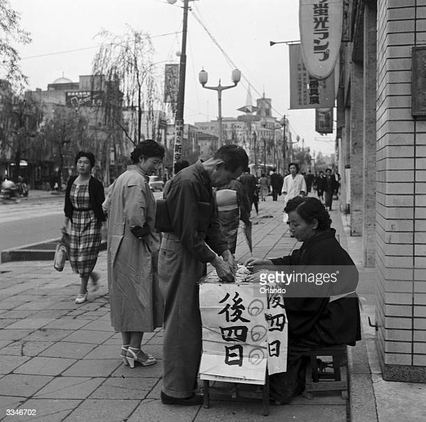 A woman selling lottery tickets on a Tokyo street The sign reads 'In Four More Days You Will Know Whether You Have Won Or Lost'