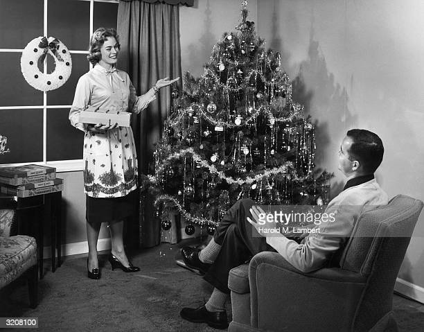 A woman smiles and points to a Christmas tree she has just decorated as a man sits in an easy chair with his legs crossed Several boxes for ornaments...