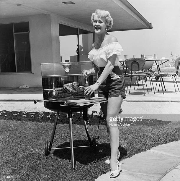 A woman smiles as she stands next to a barbecue grill in her back yard preparing to baste a roast chicken on a rotisserie spit She wears a summer...