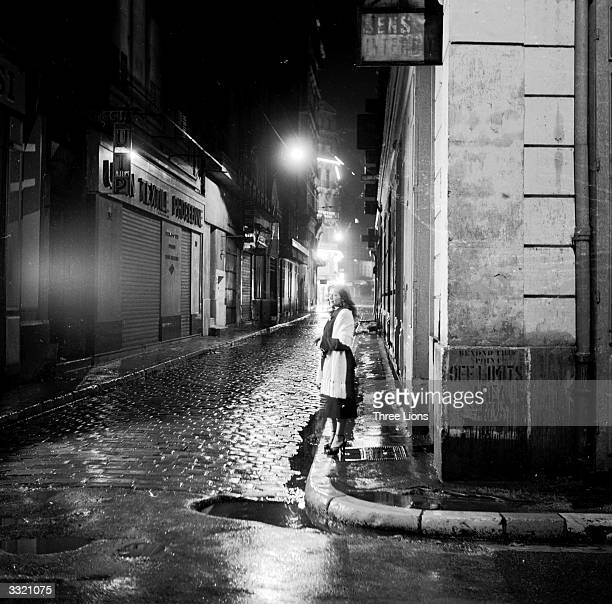 A woman stand on the corner of a wet street in Marseilles The wall signs are a reminder of the days when the city was filled with American troops