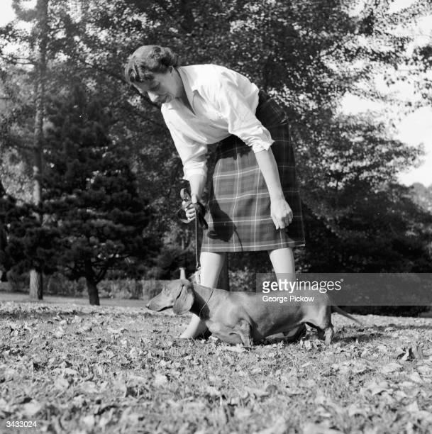 A woman taking her dachshund dog for a walk