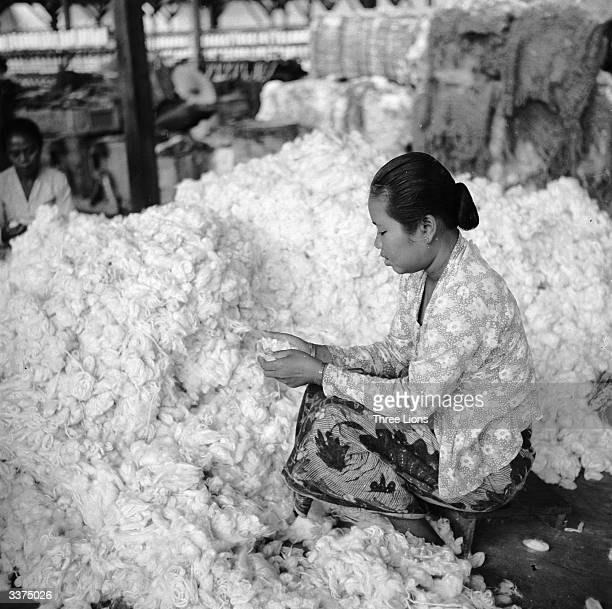 A worker at a textile factory in Bandung Indonesia prepares to spin raw cotton into skeins of yarn Some of the cotton is grown locally and the rest...