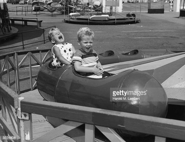 A young boy and girl scream as they sit inside a car on a roller coaster track at an amusement park