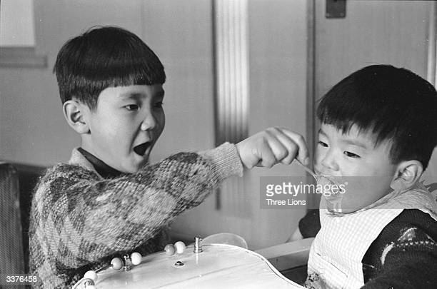 A young boy feeding his younger brother ice cream at their home in Nagasaki Japan