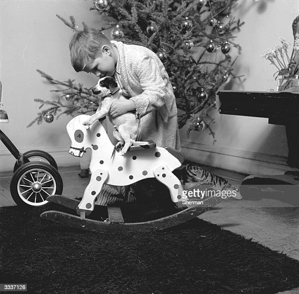 A young boy holds his puppy over a wooden rocking horse with a Christmas tree in the background