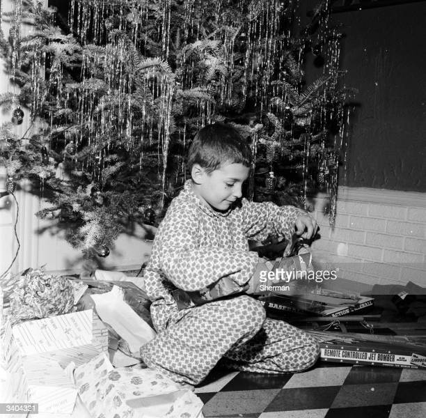 A young boy sitting under the christmas tree sets about opening his christmas gifts