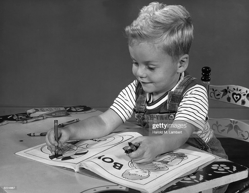 A Young Boy Smiles As He Sits Behind Desk Coloring With Crayons In