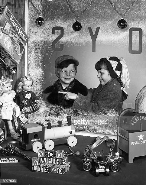 A young boy smiles mischievously as a young girl points to a doll she wants in the window display of a toy store around Christmas 1950s They wear...
