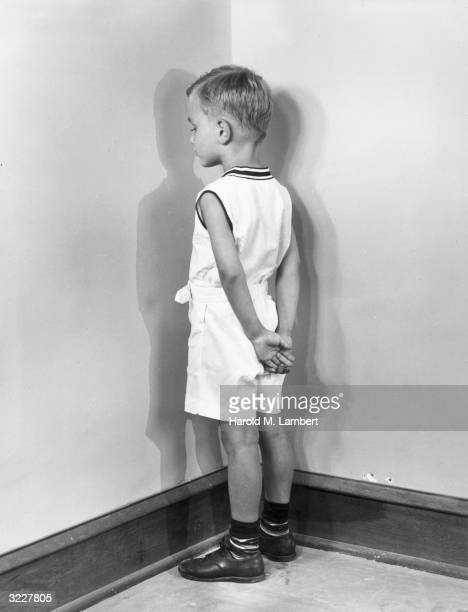 A young boy stands in a corner facing the wall with his hands behind his back as he is punished