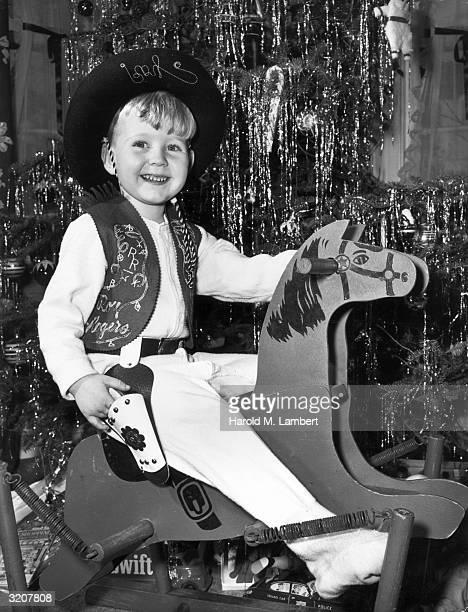 A young boy wearing a cowboy outfit smiles as he rides his new wooden rocking horse in front of the Christmas tree 1950s He wears a matching Roy...